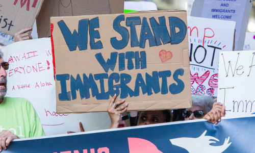 """A protestor holding a """"We Stand with Immigrants"""" sign."""